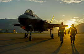 Two Airmen at sunset with F-35